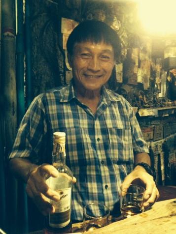 "Our bartender at ""Cheap Charlies,"" a really fun CHEAP bar in the heart of downtown bangkok"